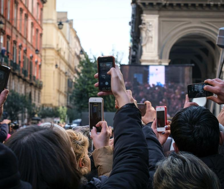 Image of a group of people taking pictures with cellphones.
